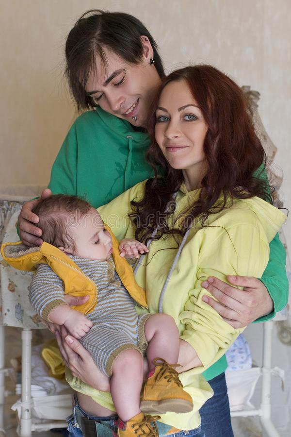 Young family mom, dad and son at home. Happy couple holding a baby. young neformal family with facial piercing. mom, dad and sleeping son at home stock images