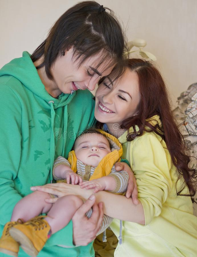 Young family mom, dad and son at home. Happy couple holding a baby. young neformal family with facial piercing. mom, dad and sleeping son at home royalty free stock images