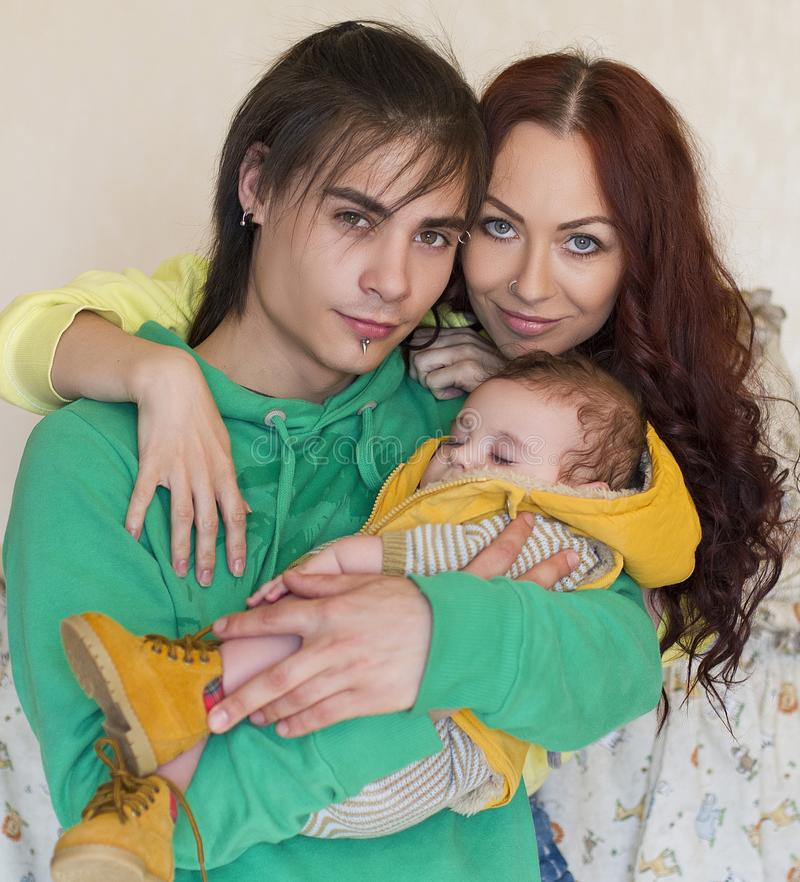 Young family mom, dad and son at home. Happy couple holding a baby. young neformal family with facial piercing. mom, dad and sleeping son at home royalty free stock photography