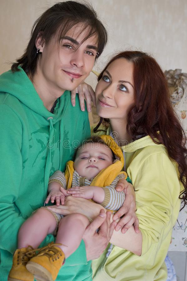Young family mom, dad and son at home. Happy couple holding a baby, wife looks at her husband in love. young neformal family with facial piercing. mom, dad and stock images