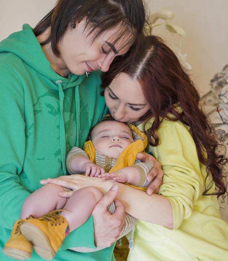 Young family mom, dad and son at home. Happy couple holding a baby, women kisses a boy. young neformal family with facial piercing. mom, dad and sleeping son at royalty free stock photos
