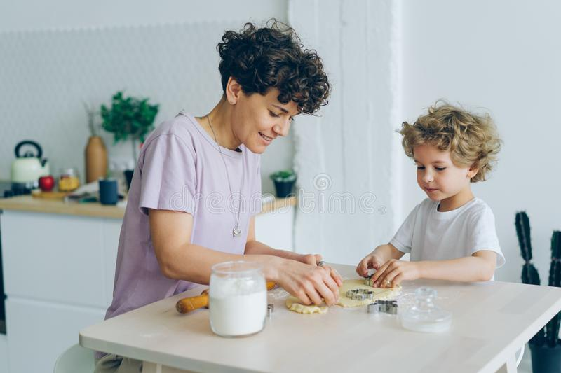 Young family mother and son making home-made cookies at kitchen table royalty free stock photography