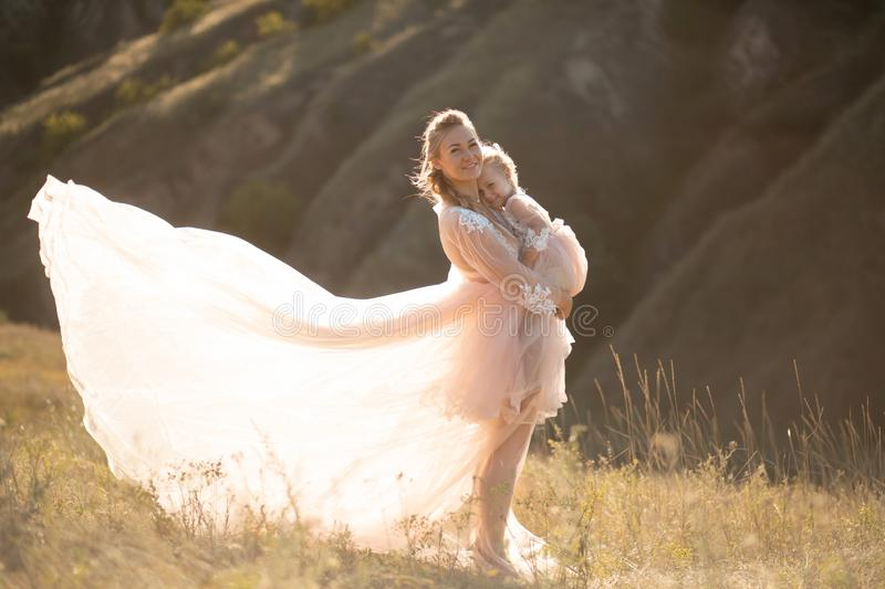 A young family in nature in identical dresses. beautiful young mom holds her daughter in her arms. Field and hills background stock images