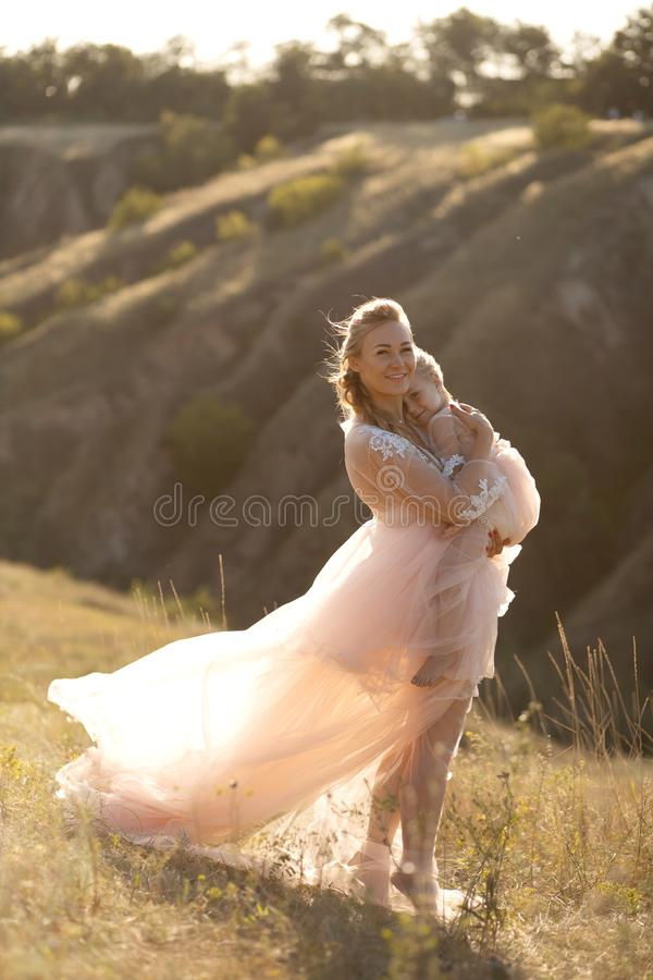 A young family in nature in identical dresses. beautiful young mom holds her daughter in her arms. Field and hills background stock photo