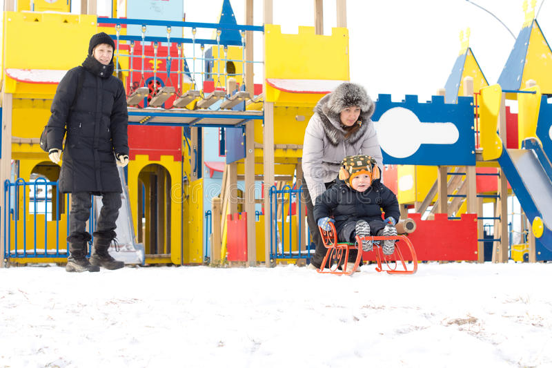 Young family out toboganning in snow royalty free stock image