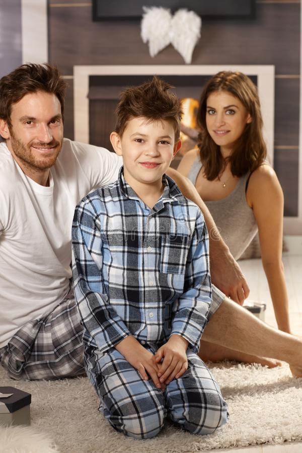 Young family in pajamas. Young family sitting on floor in pajamas, smiling stock photography