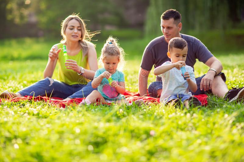 Family in park -Male and female child blow soap bubbles outdoor royalty free stock photography