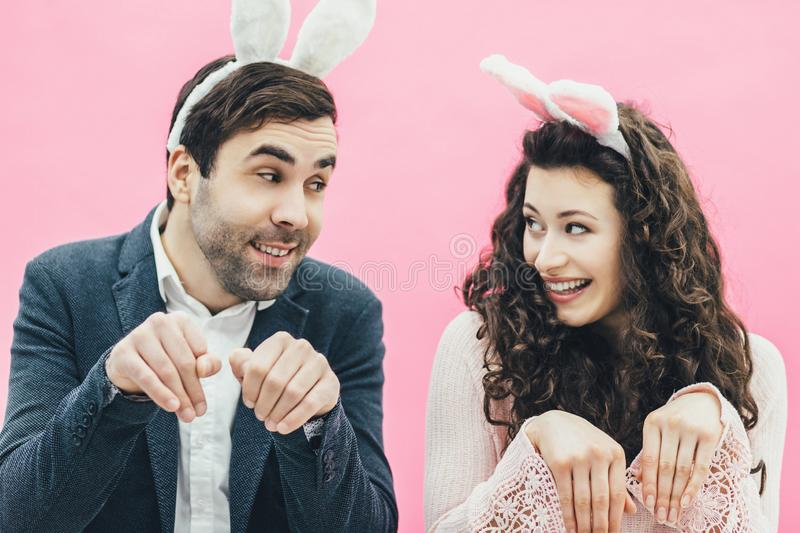 Young family on pink background. Easter Happy couple. Holiday. A tiny ear. People from the rabbit ears. Dodge doing. Young family on pink background. Easter royalty free stock photography