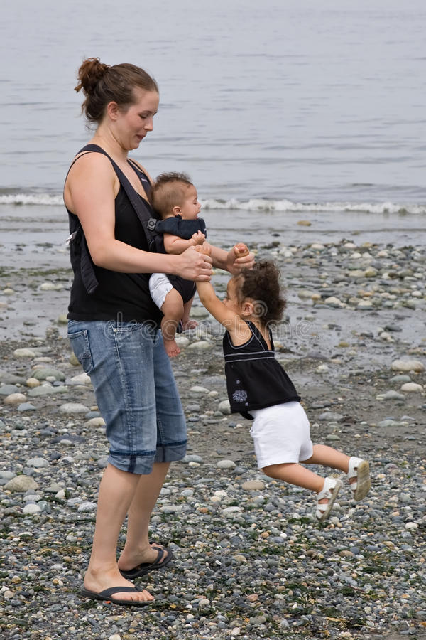 Young family playing at beach. Young single mom with her two children playing at the beach royalty free stock photography