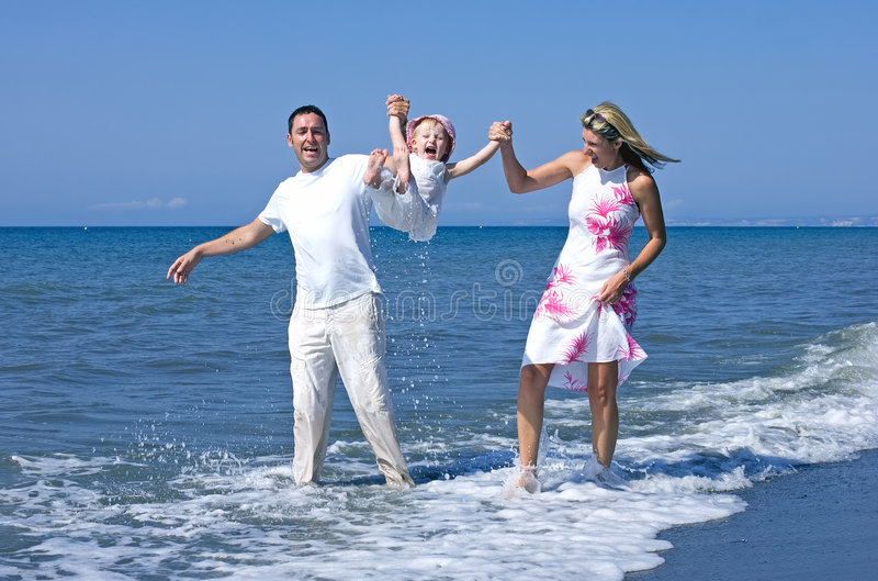 Young family playing with daughter on beach in Spain stock image