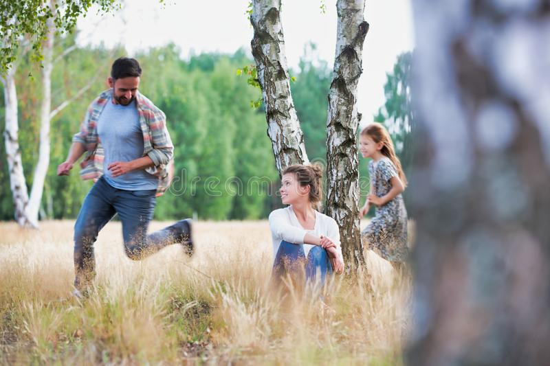 Young family playing in the forest, the little girl is chasing her father whilst the mother sits down by a tree and watches royalty free stock photos