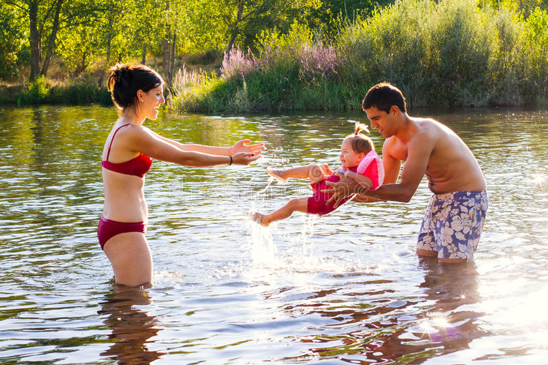 Young family playing in the water stock photography