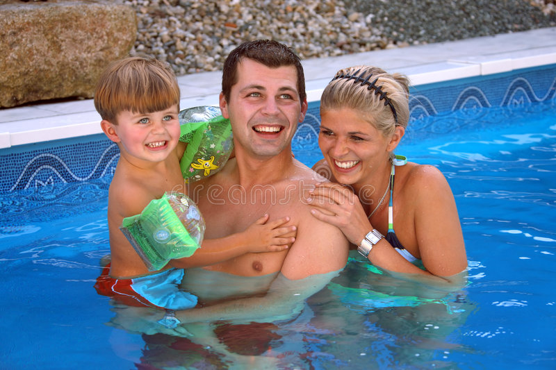 Young family in the pool stock image