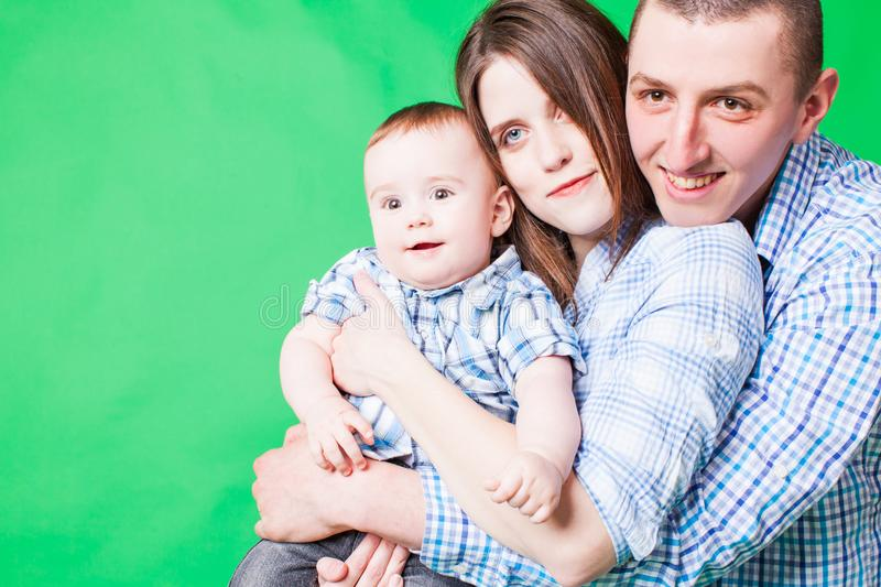 Young family portrait on a green b royalty free stock photography
