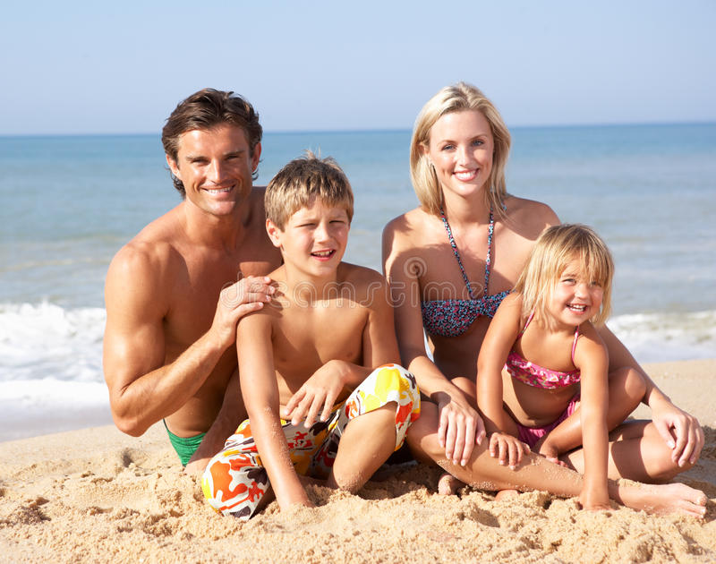 Young family pose on beach. In the sun stock photography