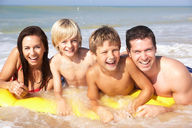 Young family pose on beach. In the sun royalty free stock photography