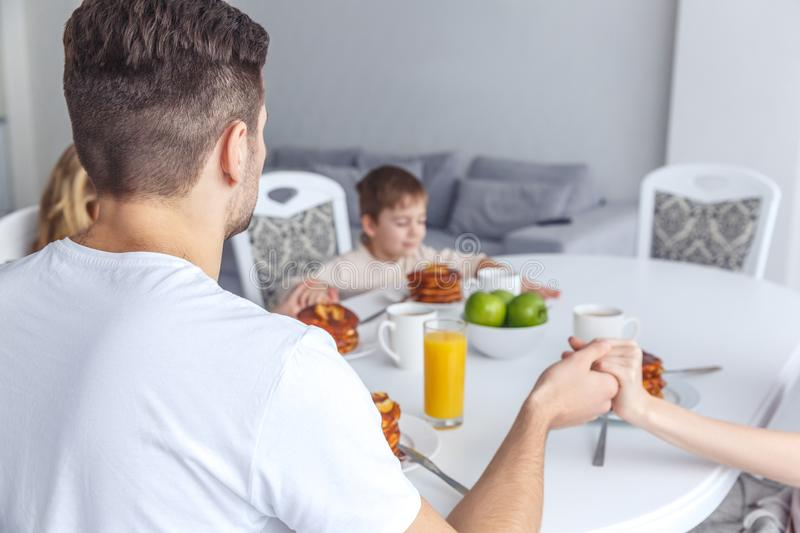 Young family praying before. Breakfast royalty free stock photo