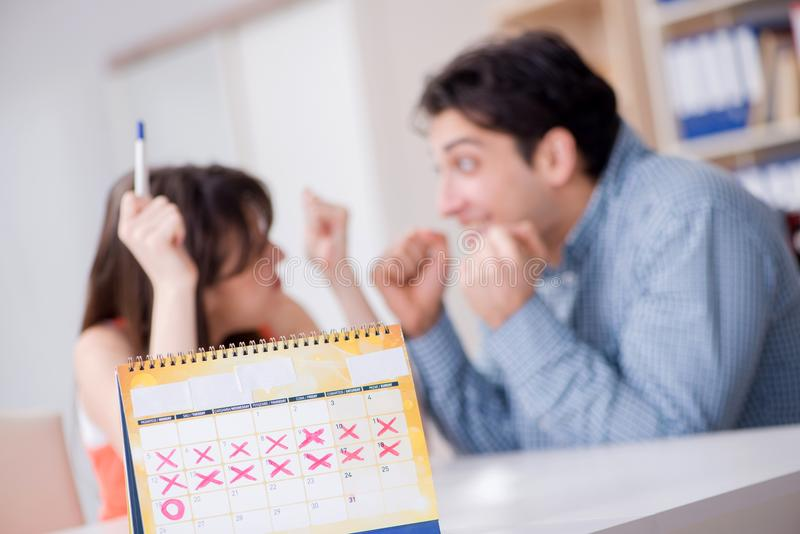 Young family in pregnancy planning concept with ovulation calend. Ar royalty free stock photography