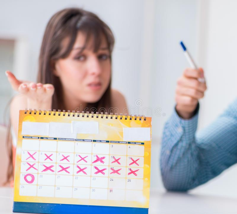 Young family in pregnancy planning concept with ovulation calend. Ar royalty free stock image
