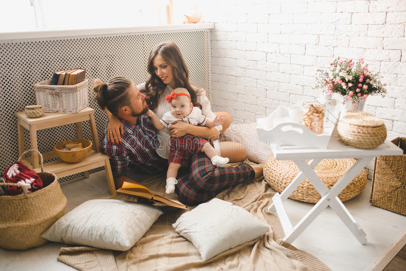 Young family reading story indoors. Parents with little baby reading story indoors stock photography