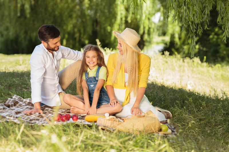 Young family relaxing in park on grass stock image