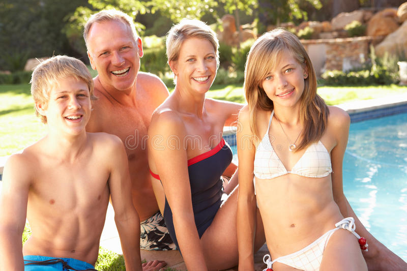 Young Family Relaxing By Pool In Garden stock photography