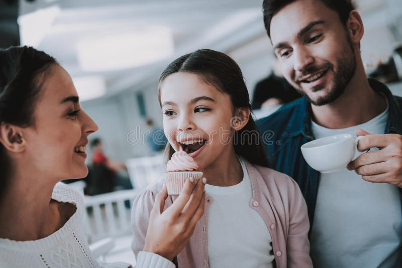 Young Family is Resting in Cafe. Family Resting in Cafe. Family is a Mother, Father and Daughter. People is Eating a Cakes and Drinking a Tea. Persons is Sitting stock photo