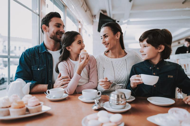 Young Family is Resting in Cafe. Family Resting in Cafe. Family is a Mother, Father, Daughter and Son. People is Eating Cakes and Drinking a Tea. Persons is stock images
