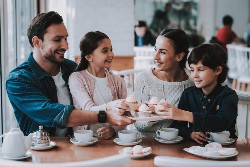 Young Family is Resting in Cafe. Family Resting in Cafe. Family is a Mother, Father, Daughter and Son. People is Eating Cakes and Drinking a Tea. Persons is royalty free stock images