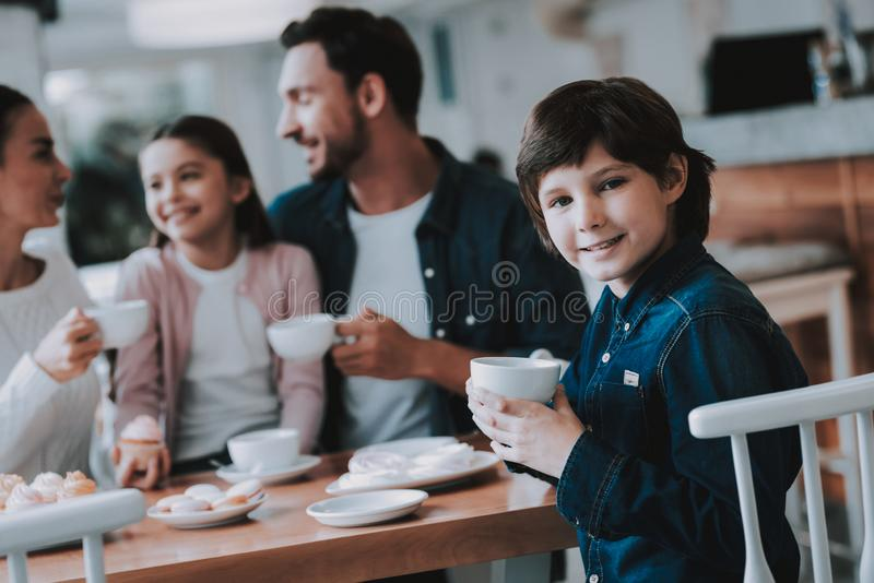 Young Family is Resting in Cafe. Family Resting in Cafe. Family is a Mother, Father, Daughter and Son. People is Eating Cakes and Drinking a Tea. Persons is royalty free stock photography