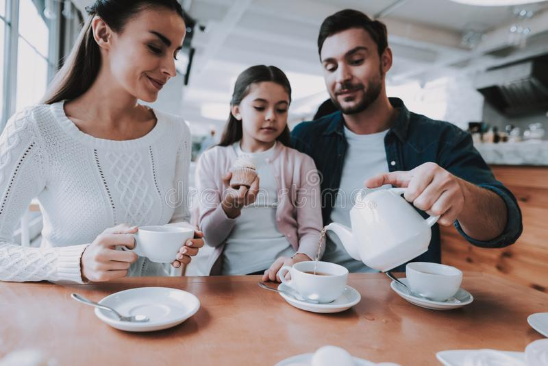 Young Family is Resting in Cafe. Family Resting in Cafe. Family is a Mother, Father, Daughter and Son. People is Eating Cakes and Drinking a Tea. Persons is royalty free stock photos