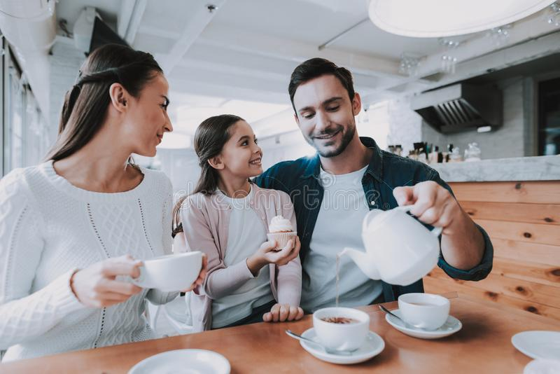 Young Family is Resting in Cafe. Family Resting in Cafe. Family is a Mother, Father, Daughter and Son. People is Eating Cakes and Drinking a Tea. Persons is royalty free stock image
