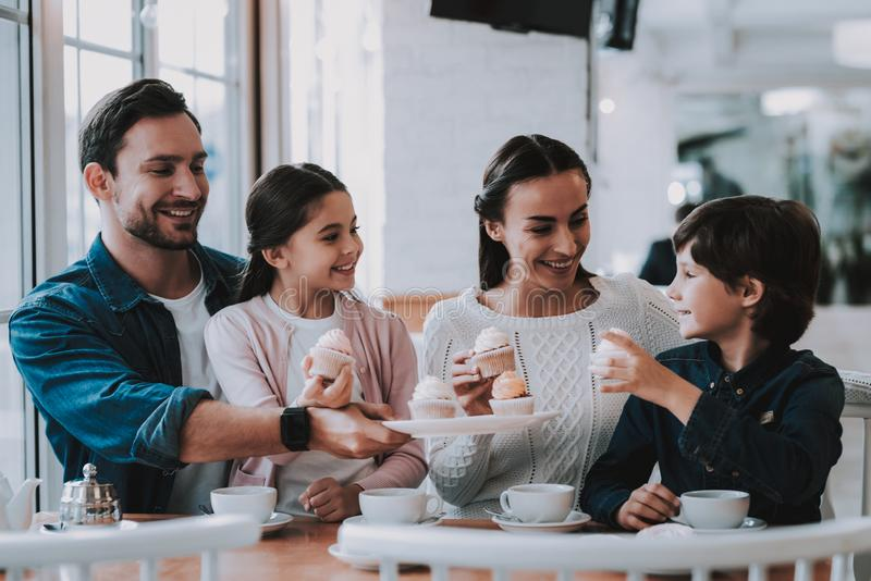 Young Family is Resting in Cafe. Family Resting in Cafe. Family is a Mother, Father, Daughter and Son. People is Eating Cakes and Drinking a Tea. Persons is stock image