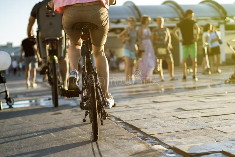 Young family riding bicycles in the city street on a summer sunny day stock photography