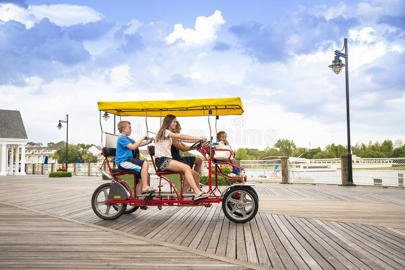 Young family riding a double surrey bicycle on a boardwalk together. Young happy family riding a double surrey tandem bicycle on a large ocean boardwalk. Outdoor stock photos