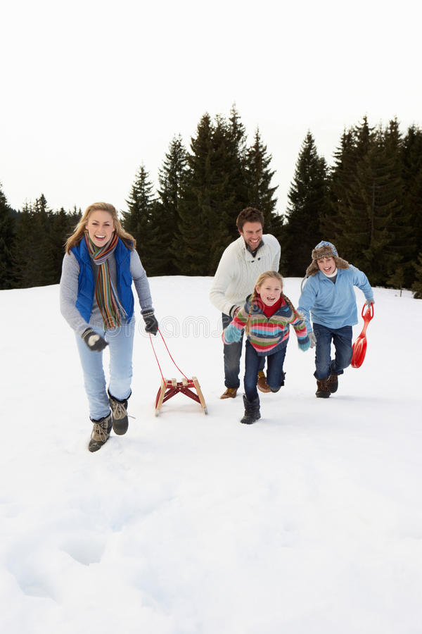 Young Family Running Through Snow With Sled stock images