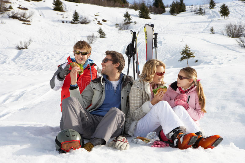 Young Family Sharing A Picnic On Ski Vacation. Smiling at each other stock images
