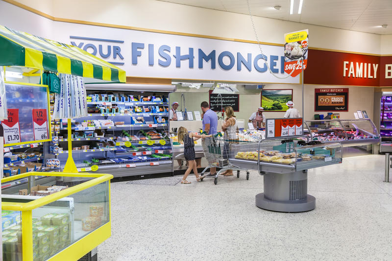Young family shopping at the fishmongers counter in Morrisons supermarket store. stock photo