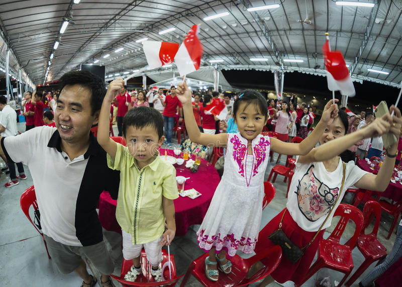 A young family sing one of the national day song and wave mini national flags with pride and joy stock photos
