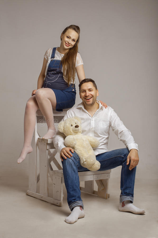 Young family sits on a ladder with Teddybear royalty free stock photo