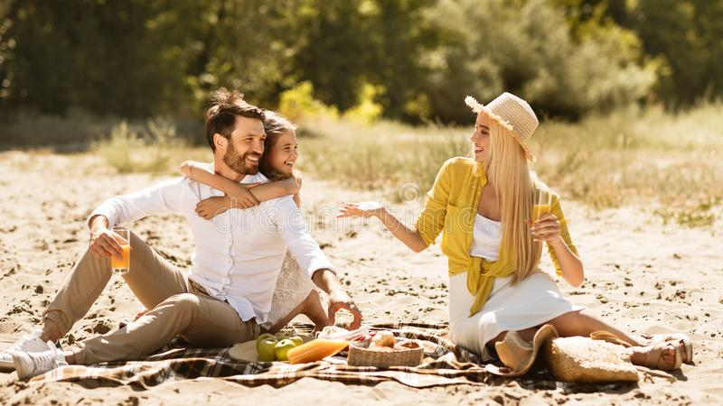 Young family sitting on blanket during picnic in nature stock images