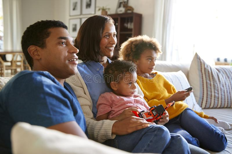 Young family sitting together on the sofa in their living room watching TV, selective focus stock photos