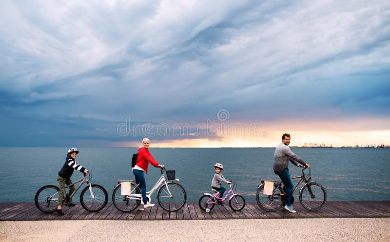 Young family with small children and bicycles outdoors on beach. Young family with small children and bicycles outdoors on beach, cycling royalty free stock images