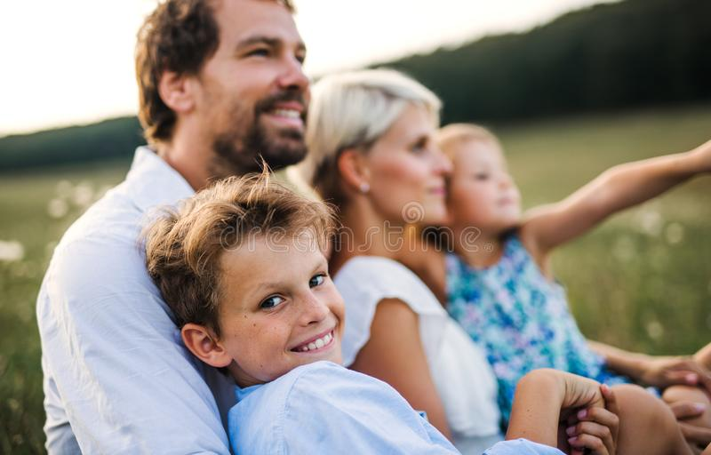 Young family with small children in summer nature at sunset. Happy young family with small children spending time together outside in green summer nature at stock photos