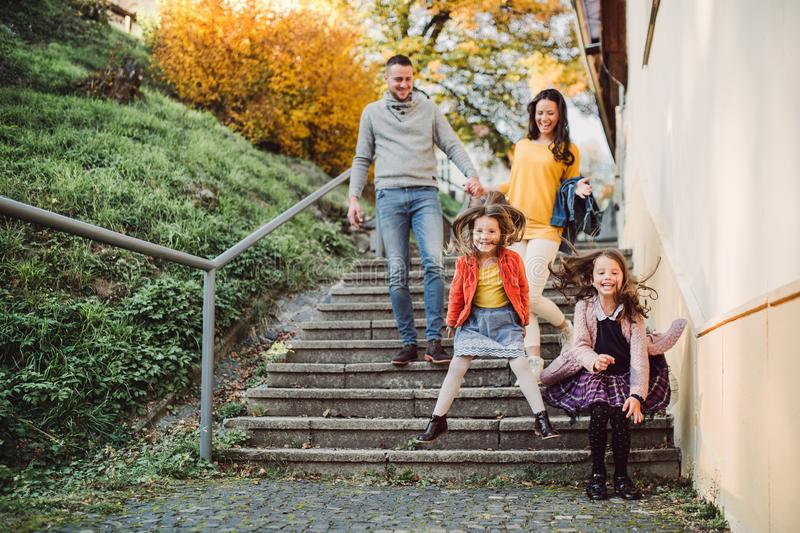 A young family with small daughter walking down the stairs outdoors in town. stock photos