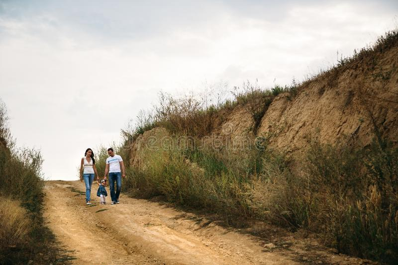Young family with a small kid walking on the country road, outdoors background royalty free stock photos