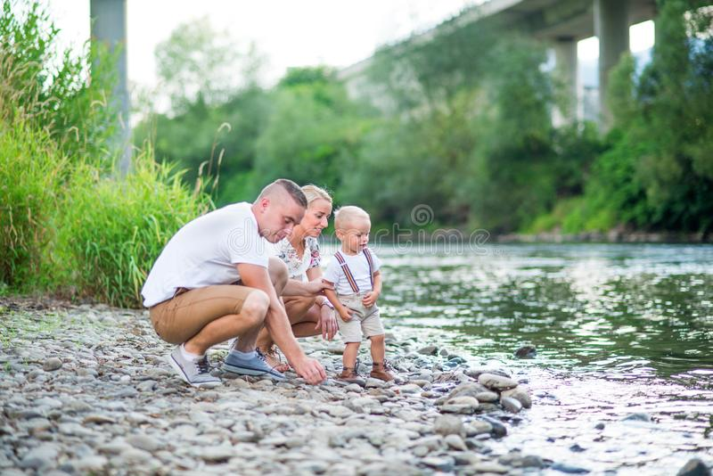 Young family with a small toddler boy in sunny summer nature, playing by river. royalty free stock photo