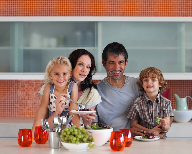 Young family smiling at camera indoors stock photo