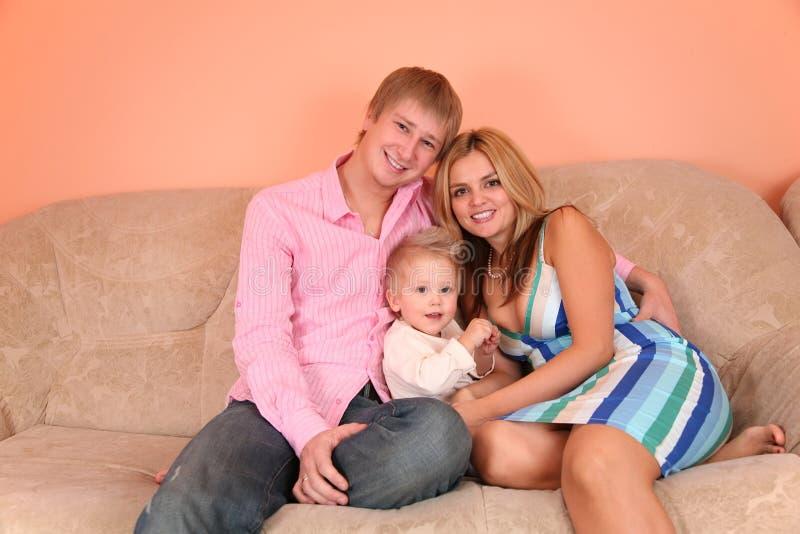 Young family on sofa 2. Young family on sofa in pink room 2 royalty free stock photos