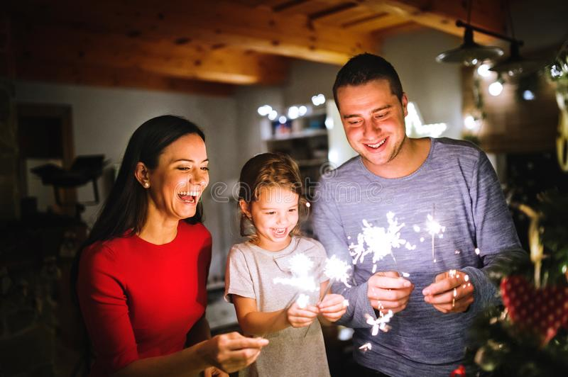 Young family with sparklers at Christmas time at home. stock photography